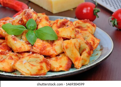 Italian traditional tortellini pasta in a plate on brown wooden table