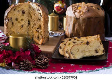 "italian typical christmas cake called ""panettone"" on table wirh christmas tools and glasses with  a wine bottle"