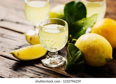 Italian typical digestive limoncello with fresh lemons, selective focus