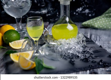Italian typical digestive limoncello with fresh lemons in smoke, selective focus
