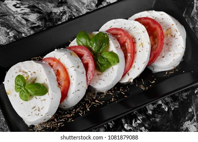 Italian typical plate called caprese, made with fresh buffalo mozzarella, tomatoes, basil, olive oil.
