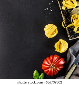 Italian vegan food concept:  tagliatelle pasta, Beefsteak tomatoes and vegan pasta recipe ingredients over stone table. Top view with copy space. Mediterranean vegetarian cuisine.