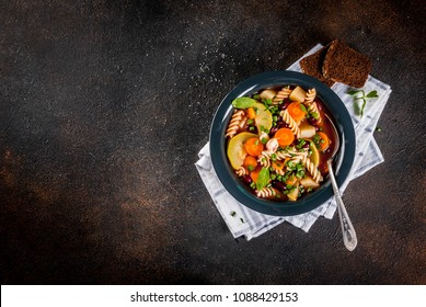 italian vegetable minestrone soup with fusilli pasta above copy space dark rusty background