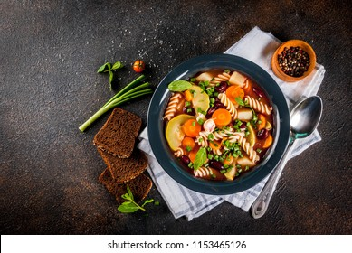 Italian vegetable soup Minestrone with fusilli pasta,  vegetarian food concept, dark rusty background, copy space