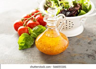 Italian vinaigrette dressing in a vintage bottle with fresh vegetables on the table.