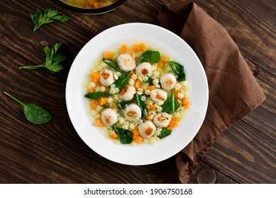 Italian wedding soup with meatballs, vegetables and small pasta in bowl over wooden background. Healthy diet dish for dinner. Top view, flat lay