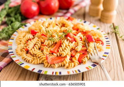 Italian whole wheat pasta fusili in tomato vegetarian sauce with sweet red peppers decorated with thyme on a wooden table.