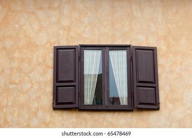 Italian windows opened on yellow wall
