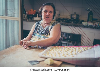 italian woman make homemade pasta gnocchi on wood board. Typical senior woman from south of Italy makes pasta from dough