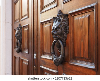 Italian wooden door with artistic doorknockers.