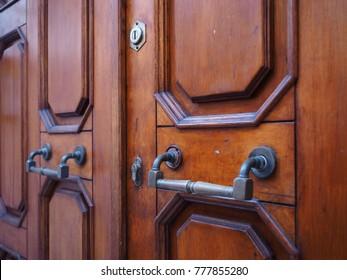 Italian wooden door, detail. Large handles and two locks.