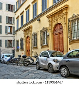 Italian yard with buildings, cars and bicycles, cobblestone patio. Yellow facade of a nice building with entrance doors decorated with carving. Car2go. Urban landscape. Italy, Florence –April 17,2018