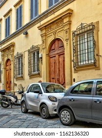 Italian yard with buildings, cars and bicycles, cobblestone patio. Yellow facade of a nice building with entrance doors decorated with carving. Car2go. Urban landscape. Italy, Florence – April 17,2018