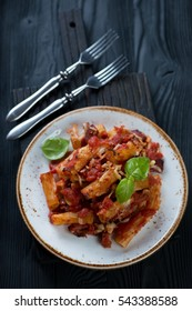 Italian ziti over black wooden background, high angle view
