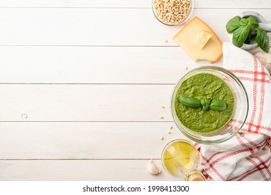 Italien cuisine. Preparing homemade italian pesto sauce. Fresh pesto in bowl with ingredients, top view flat lay on white wooden table, copy space