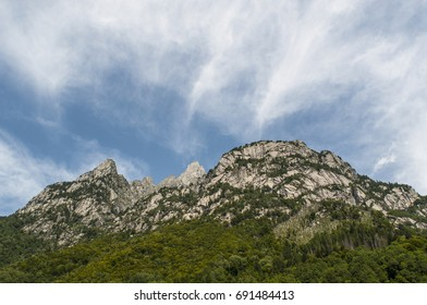 Italy, 03/08/2017: mountain peaks of the Mello Valley, Val di Mello, a green valley surrounded by granite mountains and forest trees, renamed the little italian Yosemite Valley by the nature lovers