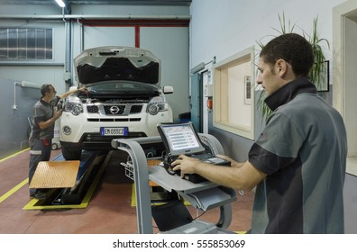 Italy; 27 July 2012, men working in a car assistance workshop - EDITORIAL