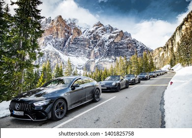 Italy, Alps, 1 May 2019: The big group of expensive sports cars does a stop on the twisting road in the Alps against snow-covered mountains Dolomite, Mercedes Benz, Porsche, BMW, sunny weather