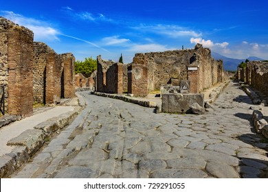 Italy. Ancient Pompeii (UNESCO World Heritage Site). Paving stones of Via Consolare. There is Mount Vesuvius in the background