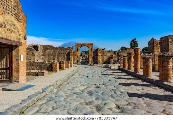 Италия. Древние Помпеи (объект Всемирного наследия ЮНЕСКО). Тротуарные камни Виа дель Форо. Есть Арка Калигулы, Виа ди Меркурио и гора Везувий на заднем плане