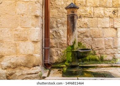Italy, Apulia, Metropolitan City of Bari, Molfetta. Old and mossy public water spigot.