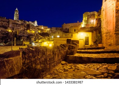 Italy, Basilicata Matera, 31 agoust 2013: Beautiful night view of a street in the ancient stone city center of  Matera, with the tower cathedral illuminated in the background.