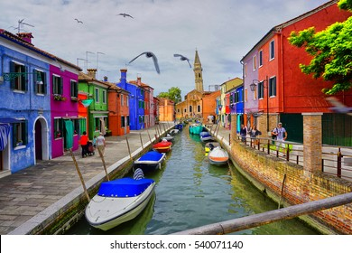 ITALY, BURANO ISLAND IN VENICE - JULY 10, 2016: The Leaning bell tower behind the canal with boats and colorful houses