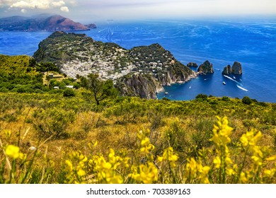 Italy. Capri Island. The main town Capri and easten part of island with Faraglioni (rock formation) seen from Monte Solaro. There is Sorrentine Peninsula in the background (on left)