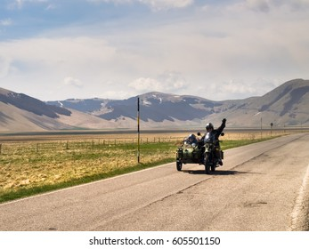 Italy, Castelluccio di Norcia - April 25, 2015: Motorcyclists on the road of big plan of Monti Sibillini. Motorcyclists in a vehicle sidecar salute as they pass.