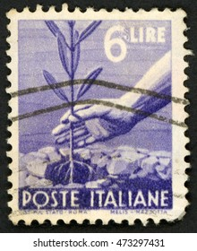 ITALY - CIRCA 1947: post stamp printed in Italy shows right hand putting plant of olive tree into the ground; planting tree; Scott 472A A257 6 lire violet; circa 1947
