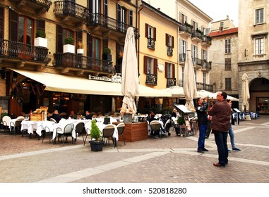 ITALY. COMO - APRIL 21 2016: Tourists in a street cafe in the Piazza del Duomo on the background of old houses.