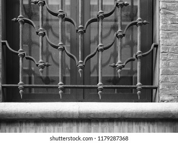 Italy, detail of a window. Artistic railing and part of Renaissance house wall. Black and white photo.