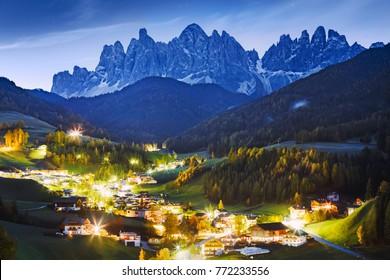 Italy, Dolomite Alps. Fabulous night landscape of small scenic village  Santa Maddalena - Magdalena at alpine mountain ridge background. Lit scenic valley at twilight. Charming Autumn season in Alps.