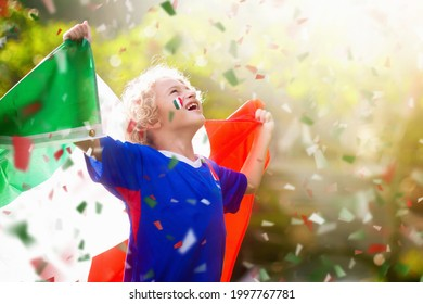 Italy football fan. Italian kids play soccer on outdoor field. Cheering team fans celebrate victory. Children score a goal at football game. Little boy in Italia jersey kicking ball on outdoor pitch. - Shutterstock ID 1997767781