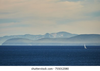 Italy. The island of Elba. A sailboat in the background of far coast and hills
