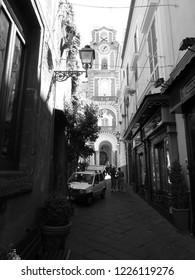 Italy Italian Riviera Sorrento Amalfi Coast people in narrow alley with car church at the end black and white