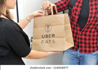 Italy - Milan july 22,2018 uber eats home delivery - you can order food from the restaurant and eat it at home, at work or in other places - lady gets the food in a bag