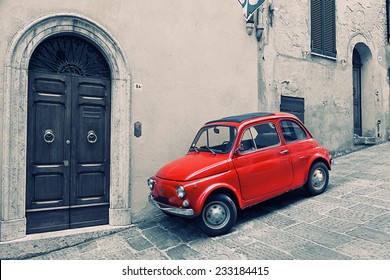 ITALY, MONTEPULCHANO - MAY 16, 2014: Old red Fiat 500 R to stand near a wall. Fiat Nuova 500 (ital. cinquecento) - the car made by the Fiat company with 1957 on 1975