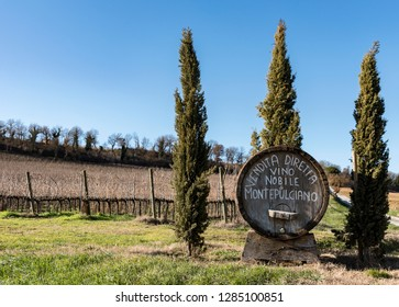 """Italy, Montepulciano, 14 January 2019: wooden barrel with writing """"montepulciano noble wine sale"""" autumn vineyard background"""