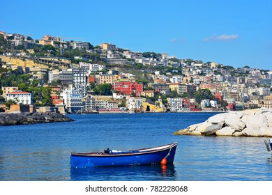 Italy, Naples, fishing boat in the small port of Riva Fiorita with Posillipo hill in the background.