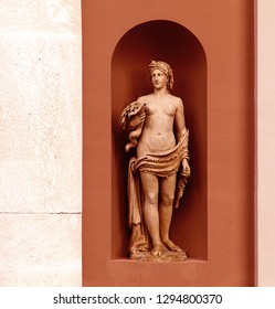 Italy, neoclassical mythological statue of a goddess in a niche of an antique building facade