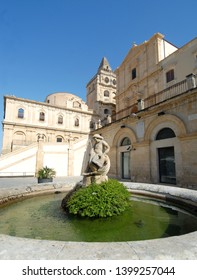 Italy / Noto - April 28, 2013: round fountain with little angel and in the background the baroque church with large staircase of San Francesco d'Assisi all'Immacolata.