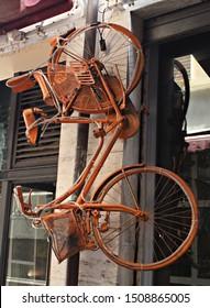 Italy: Orange hanging bicycle .