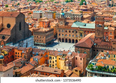 Italy Piazza Maggiore in Bologna old town tower of town hall with big clock and blue sky on background, antique buildings terracotta galleries.