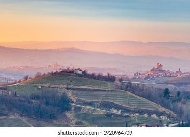 Italy Piedmont: wine yards unique landscape at sunset, Serralunga d'Alba medieval castle on hill top, La Morra and Castiglione Falletto villages, the Alps in the background, italian heritage