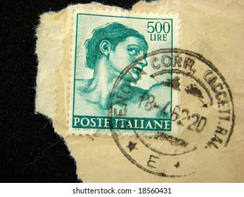 Italy postage stamp with a piece of envelope, on black background