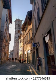 Italy, Prato - July 07 2017: the view of the bell tower at the end of the narrow street in Prato on July 07 2017, Tuscany, Italy.