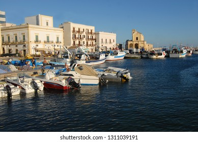 Italy / Puglia – August 1, 2010: Gallipoli is a town of Salento on the coast of Puglia. The historic center is on an island offshore. In the ancient port the atmosphere is Mediterranean.