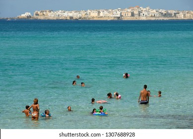 Italy / Puglia – August 19, 2010: beach in front of Gallipoli in Puglia. Gallipoli is a town of Salento on the coast of Puglia. The historic center is located on an island offshore.