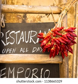 Italy, Puglia Region. Traditional restaurant blackboard with red peppers.